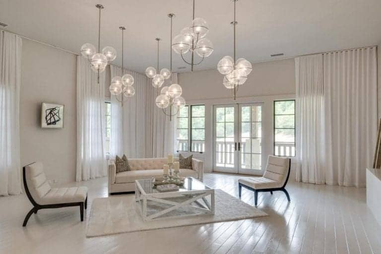 This living room boasts white walls and floors, along with a white ceiling where the lovely pendant lights are hanging from. The room offers a white couch and charming white window curtains.