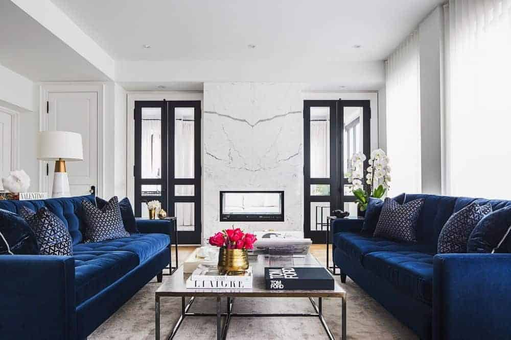 This living room boasts a pair of elegant blue couches with a large center table in between. The room has a large gray area rug and a fireplace too.