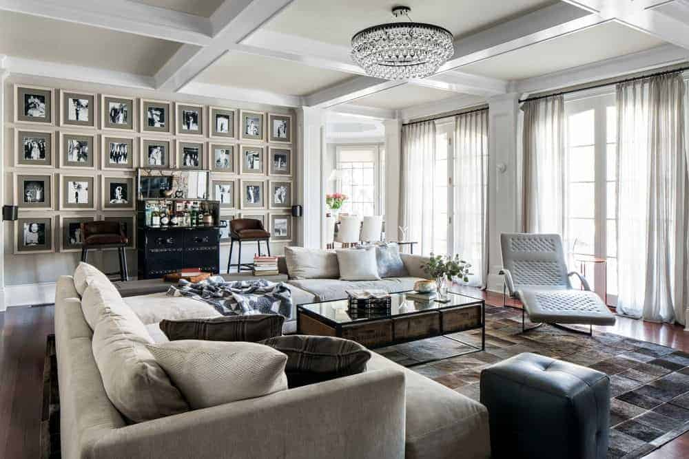 A spacious living room featuring a stunning coffered ceiling and a gorgeous ceiling light, along with a cozy large couch set on a stylish gray rug.