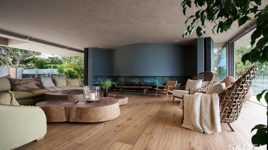 Huge modern living space with a gray ceiling and hardwood flooring. The room offers a stylish set of seats and a stunning wooden center table.