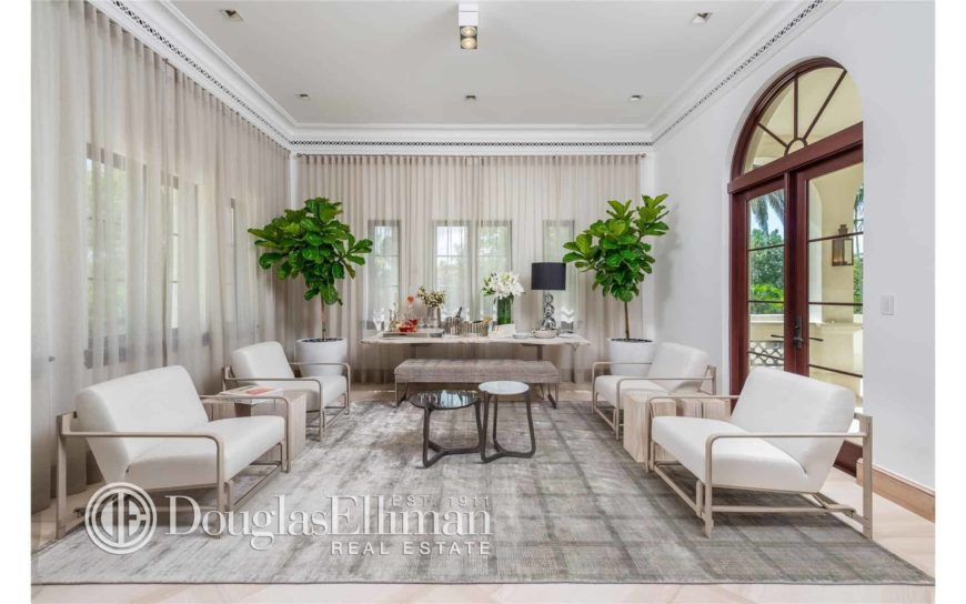 Large living space with lovely window curtains and a large stylish gray area rug where the classy set of seats and center table are set.
