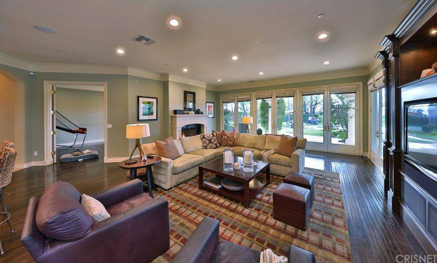Huge family living space with a large sofa set and a couple of purple seats. There's a large fireplace and bright recessed ceiling lights, along with hardwood flooring topped by a stylish area rug.