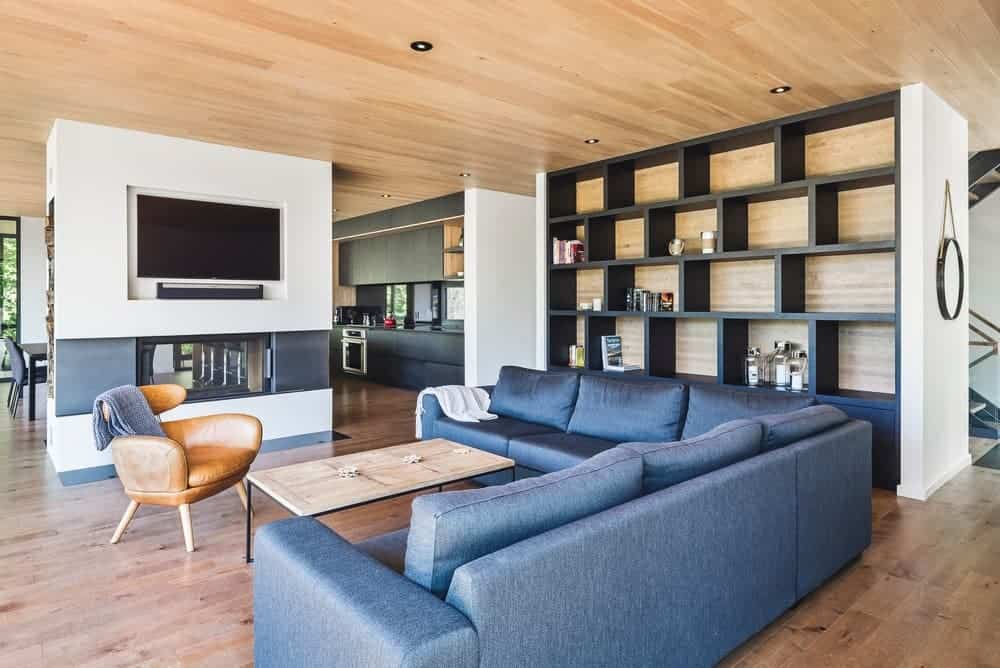 Spacious living room featuring a blue L-shaped sofa set along with a fireplace and a large flat-screen TV on the wall. There's also a built-in shelving on the side of the room.