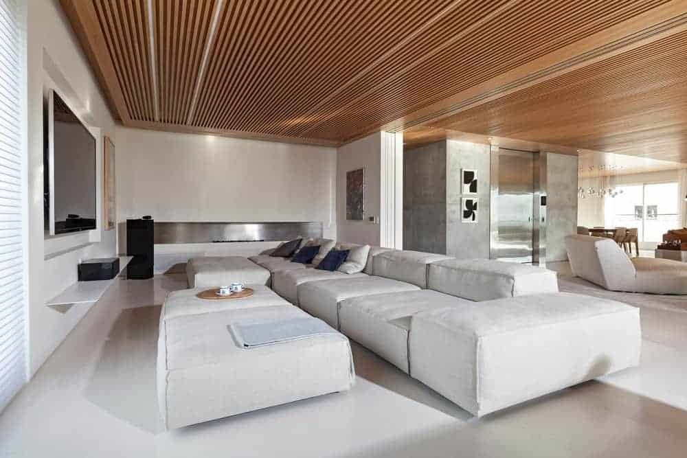 Large living space with a large modern sofa set and a large white ottoman, along with a theater-style TV in front.