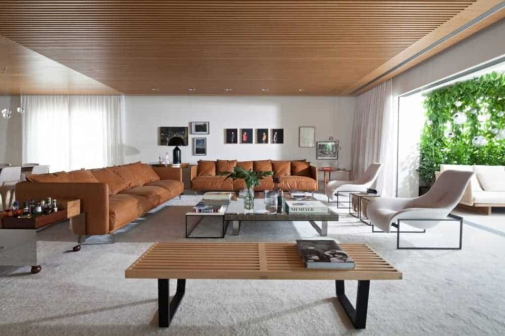 Huge living space with a pair of brown couches and a large center table set on carpet flooring. There's a way leading straight to the home's outdoor area as well.
