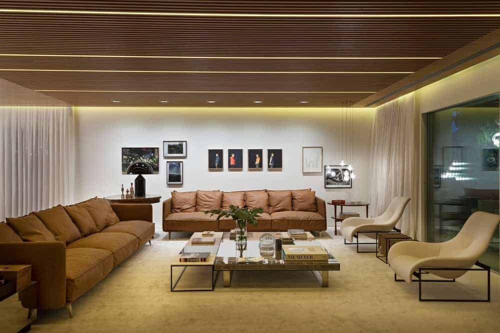 Large living room featuring a modish set of brown couches and comfy lounging chairs along with a stylish center table set on the home's carpet flooring.