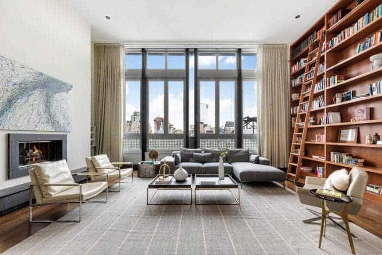 Large formal living room with a large bookshelf with a ladder and a fireplace on the other side of the room. The area offers modern seats and a large area rug covering the hardwood flooring.