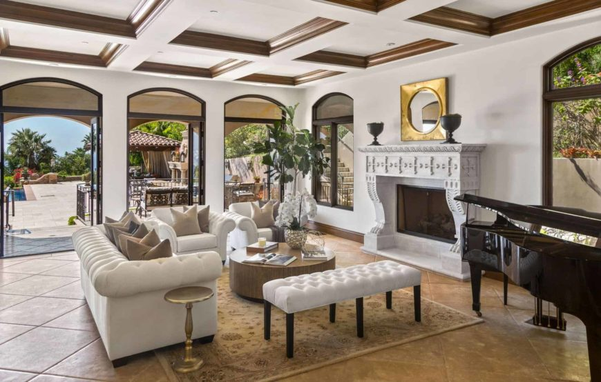 Mediterranean formal living room boasting elegant white seats and a large fireplace, along with a black piano on the side, set under the home's beautiful coffered ceiling.