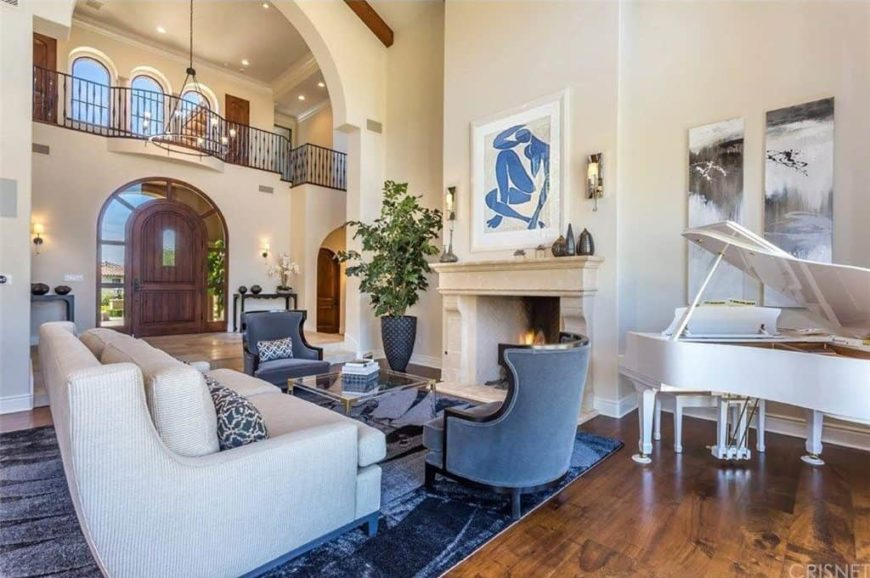 A formal living room boasting a comfy white couch with two beautiful seats alongside, set on top of a stylish area rug covering the hardwood flooring. The home also has a fireplace and a white piano.