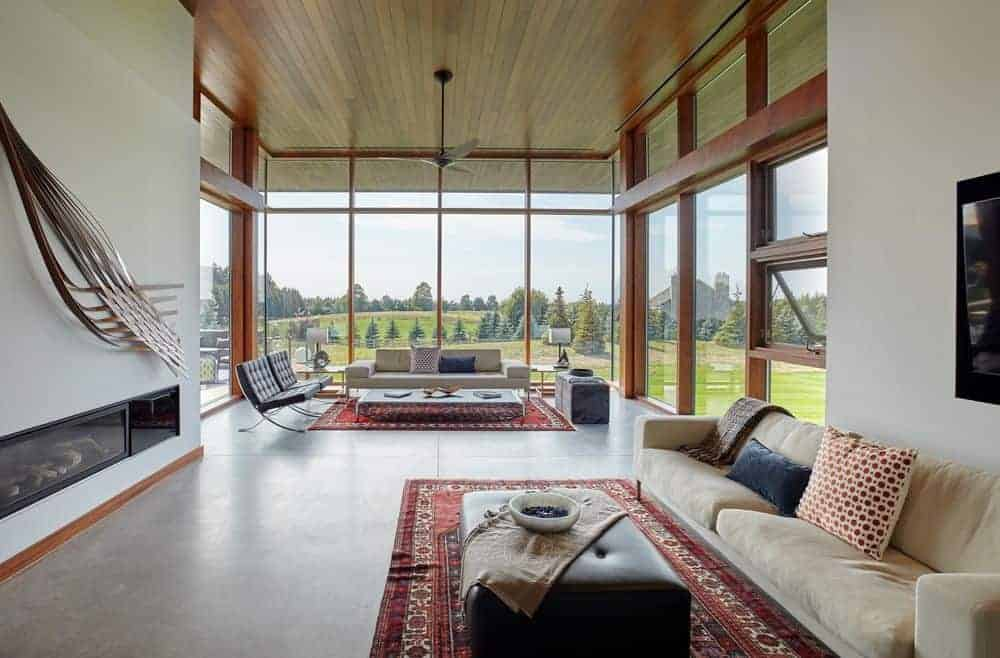Large living room boasting two areas. There's a living space area near the tall glass windows overlooking the peaceful surroundings, and there is another living space in front of the fireplace.