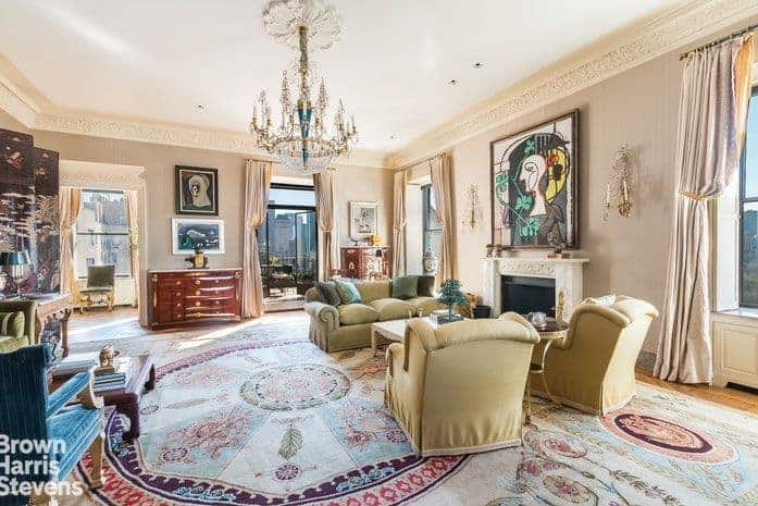 Large formal living room featuring elegant wall decors along with classy seats and a large stylish area rug. The room is lighted by a glamorous chandelier and has a fireplace too.