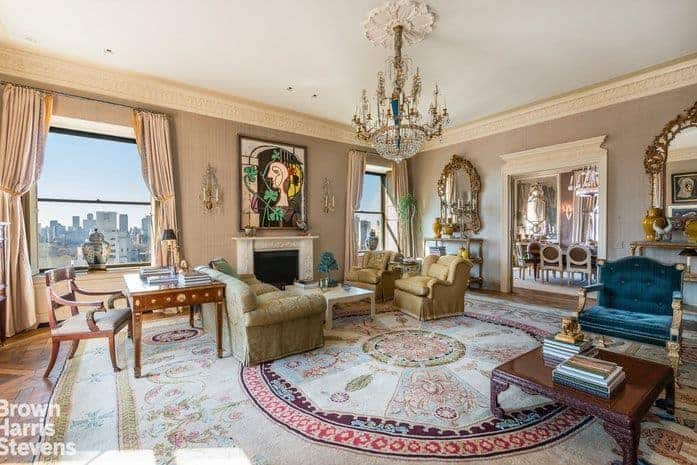 Large formal living room with classy walls and elegant pieces of furniture and wall decors. The room offers a fireplace and a glamorous chandelier.
