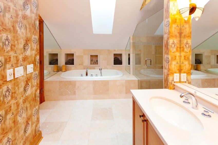 The bright master bathroom features a sink vanity and deep soaking tub underneath the skylight clad in beige marble tiles that extend to the flooring.
