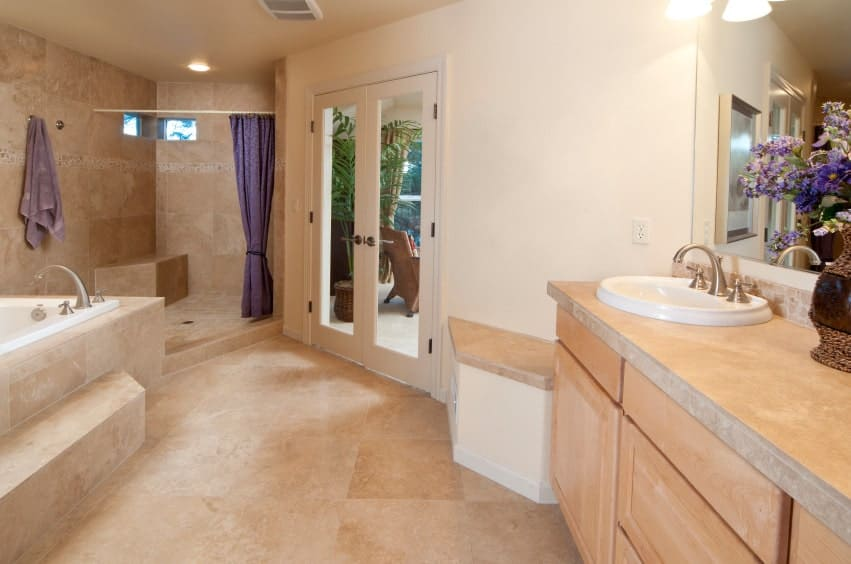 Mediterranean master bathroom with a deep soaking tub and shower area enclosed in purple curtain. It includes a light wood sink vanity with a built-in seat on the side.