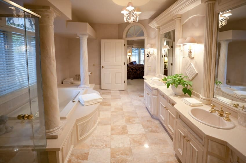 A white wooden door opens to this master bathroom with a drop-in bathtub and dual sink vanity fitted with brass fixtures and hardware. It is illuminated by a chandelier and matching sconces mounted on the beige walls.