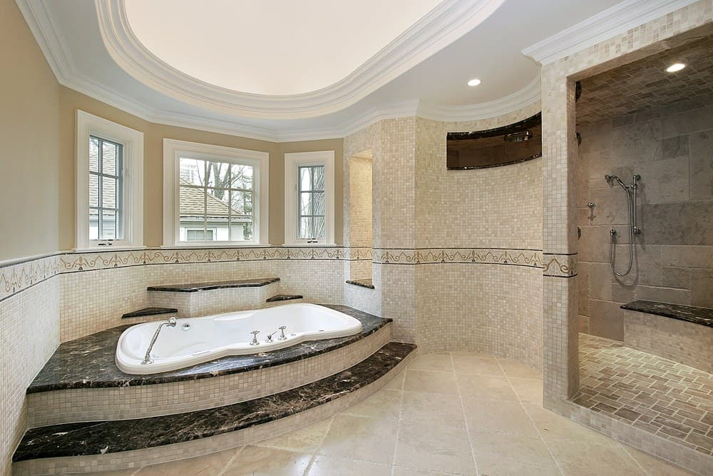 Airy master bathroom with oval tray ceiling and beige walls dominated by stunning mosaic tiles. It has a drop-in bathtub and an open shower area with a tiled bench topped with a black marble counter.