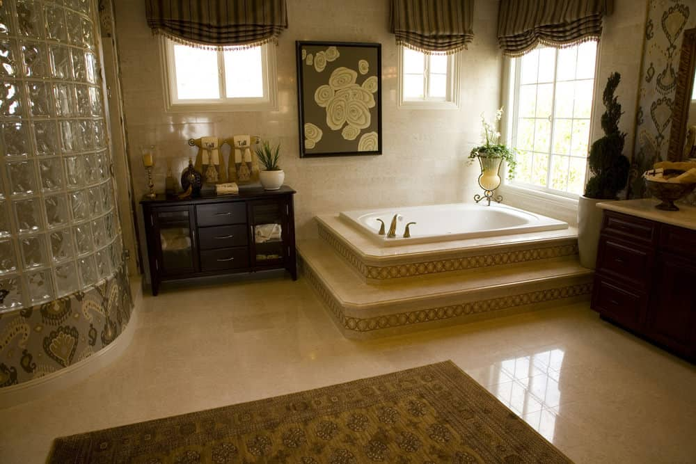 Lovely floral wall art adds a nice accent in this beige master bathroom with a deep soaking tub and walk-in shower enclosed in textured glass blocks.