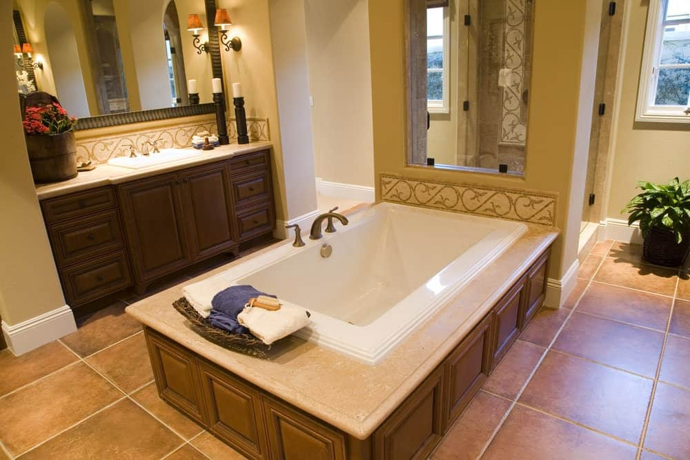 Warm master bathroom offers a single sink vanity lighted by an ornate sconce along with a drop-in bathtub clad in dark wood wainscoting.