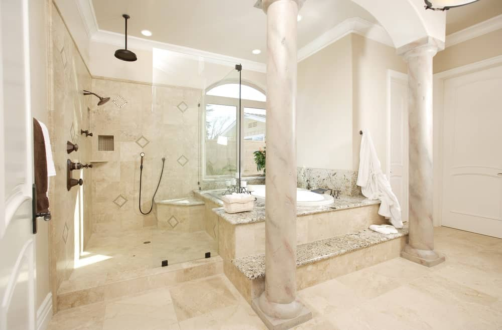 Mediterranean master bathroom with a walk-in shower and a drop-in bathtub lined with large columns. It has tiled flooring and an arched window that invites natural light in.