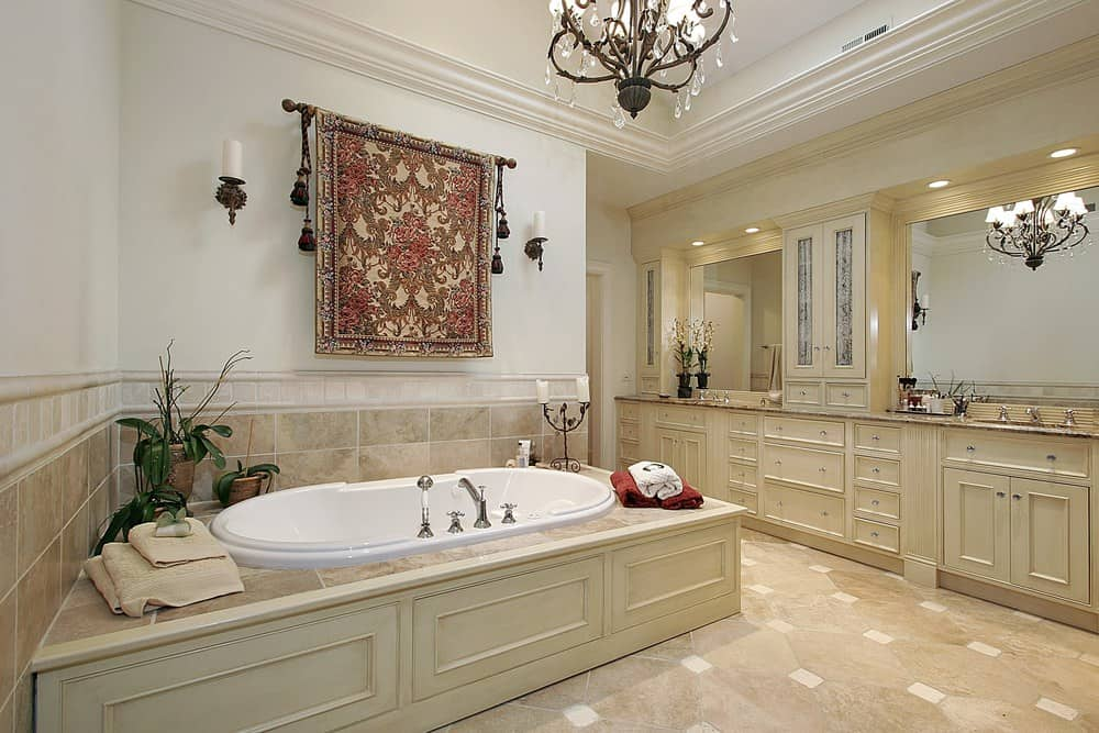 Elegant master bathroom decorated with a fancy chandelier and a gorgeous tapestry with tassels that hung above the deep soaking tub accented with fresh potted plants.