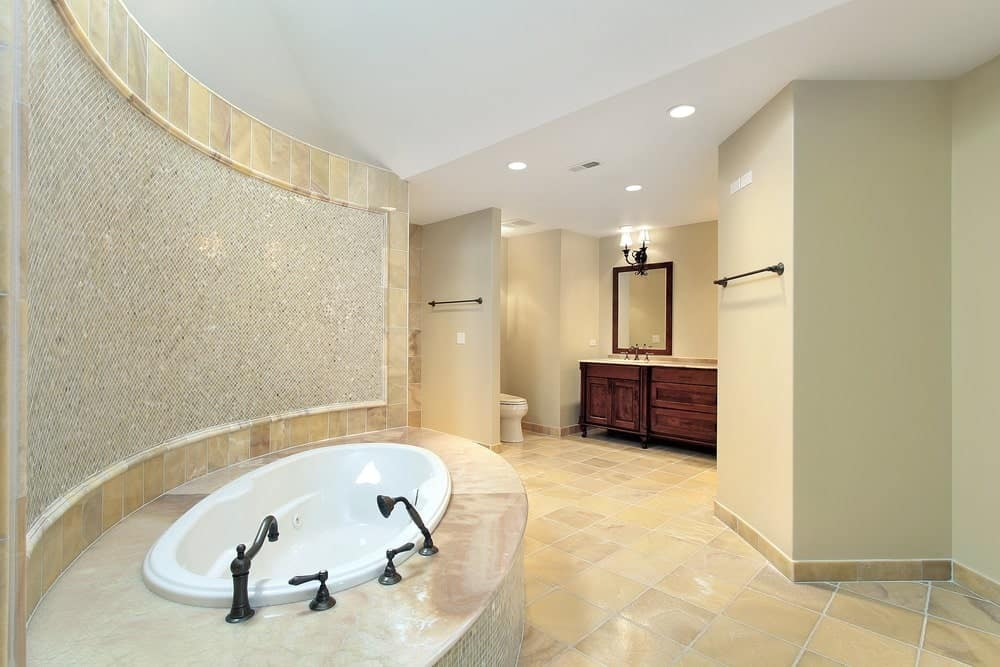 Sparkling mosaic tiles set a classy backdrop to the drop-in tub fitted with wrought iron fixtures. This room has a toilet area and wooden sink vanity lighted by sconces and recessed ceiling lights.