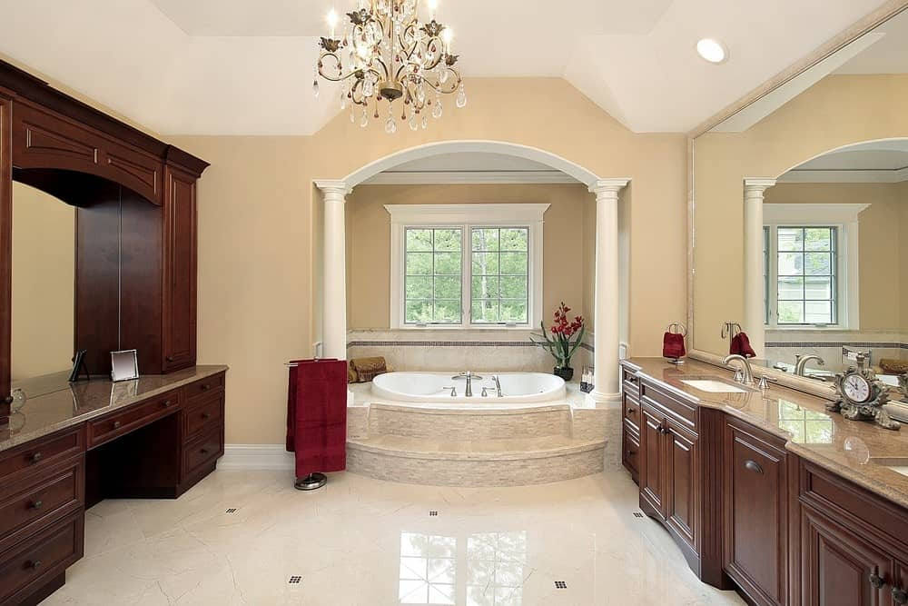 This master bathroom offers an alcove bathtub and wooden vanities facing each other. It is illuminated by a fancy chandelier that hung from the vaulted ceiling.