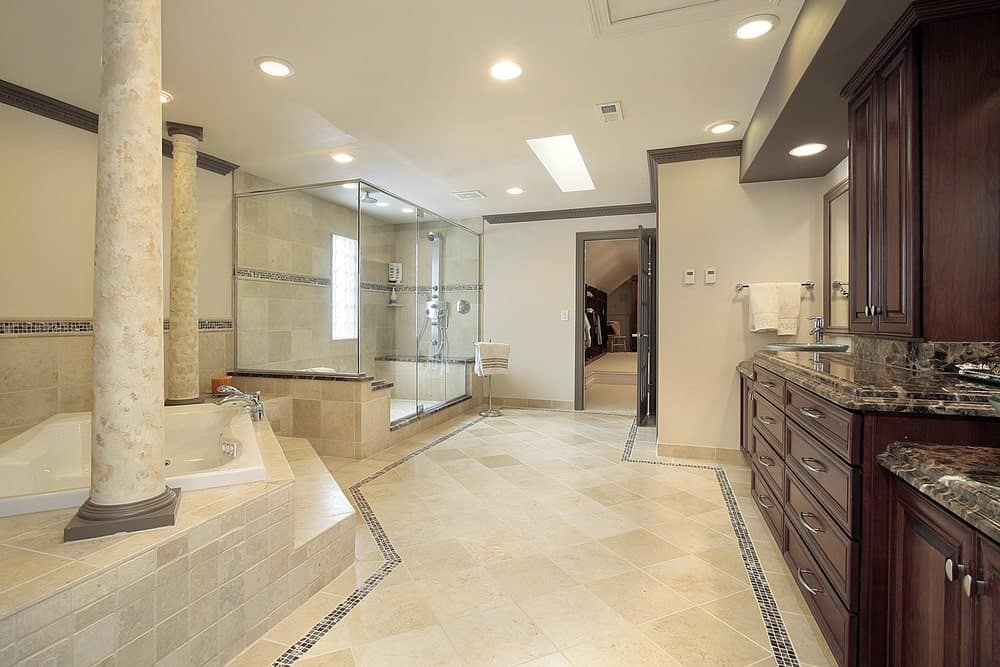The beige master bathroom showcases a walk-in shower and drop-in tub lined with a pair of columns. It includes a large dark wood vanity topped with black granite counters.