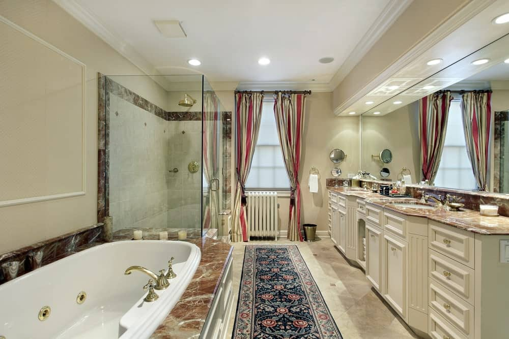 Red striped curtains and a lovely floral runner stands out in this beige master bathroom with a drop-in tub and dual sink vanity topped with elegant marble counter.