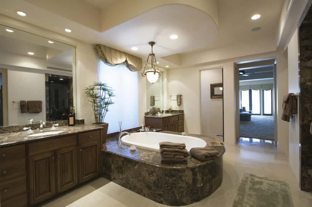 A glass pendant light hangs over the deep soaking tub clad in black granite tiles. It is situated in between dark wood vanities that are paired with frameless mirrors.