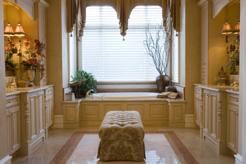 This master bathroom showcases facing vanities with tufted ottoman in the middle over marble flooring. It includes a drop-in tub by the glazed window dressed in charming valances.