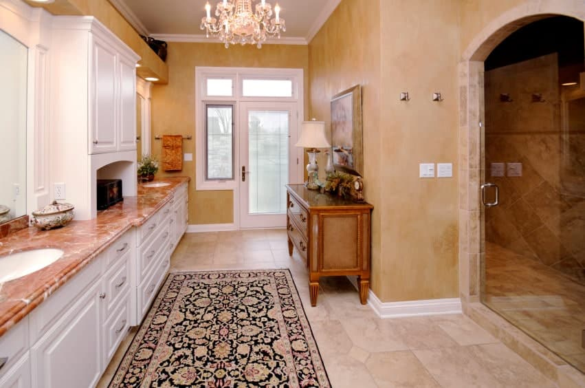 Elegant marble countertop provides a warm contrast to the white vanity fitted with dual sink. This room has an arched door and tiled flooring topped with a classy floral rug.