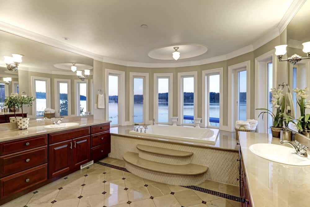 This master bathroom features redwood sink vanities with frameless mirrors on top mounted with chrome sconces. There's a drop-in tub by the glass paneled windows overlooking the serene outdoor view.