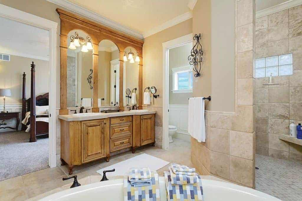 Bright master bathroom completed with a shower and toilet area along with a deep soaking tub that faces the wooden sink vanity fitted with wrought iron fixtures.