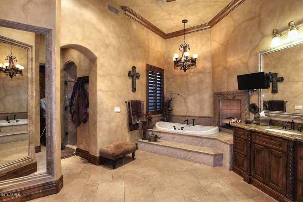 Mediterranean master bathroom with sink vanity and a brick fireplace fixed above the drop-in bathtub. It is lighted by a vintage chandelier that hung from the regular ceiling lined with wooden crown molding.