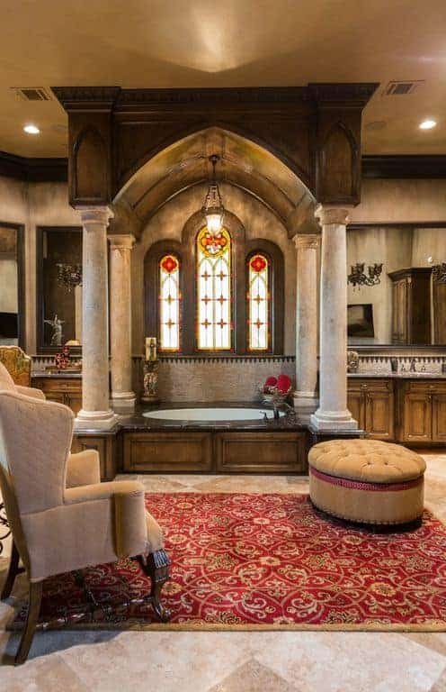 A beige wingback chair faces the round tufted ottoman that sits on a red patterned rug. There's a drop-in bathtub by the three-panel arched windows framed in distressed white columns.