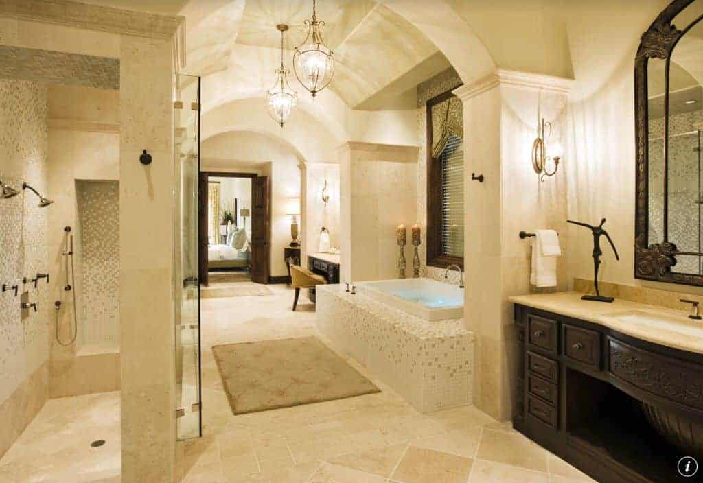 Well-lit master bathroom boasts carved wood vanities with a deep soaking tub in the middle that's clad in mosaic tiles matching with the walk-in shower's walls.