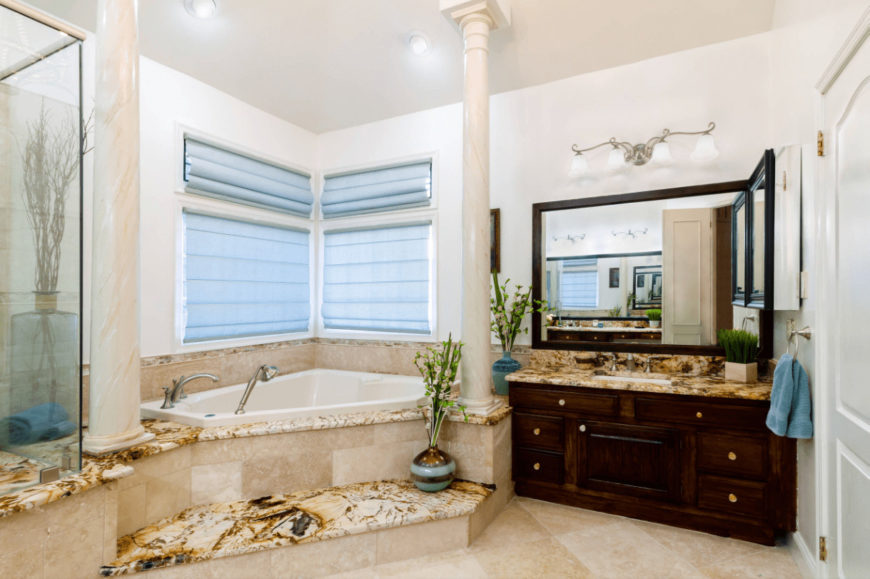 Mediterranean master bathroom with tiled flooring and glazed windows covered in light blue roller blinds. It includes a dark wood vanity and corner tub lined with marble columns.