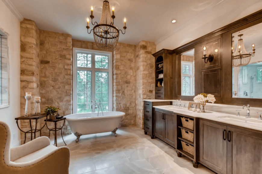 A stone brick wall adds texture in this master bathroom with a cozy seat and clawfoot tub lighted by an oversized chandelier. It includes natural wood vanity with white marble countertop and dual sink.