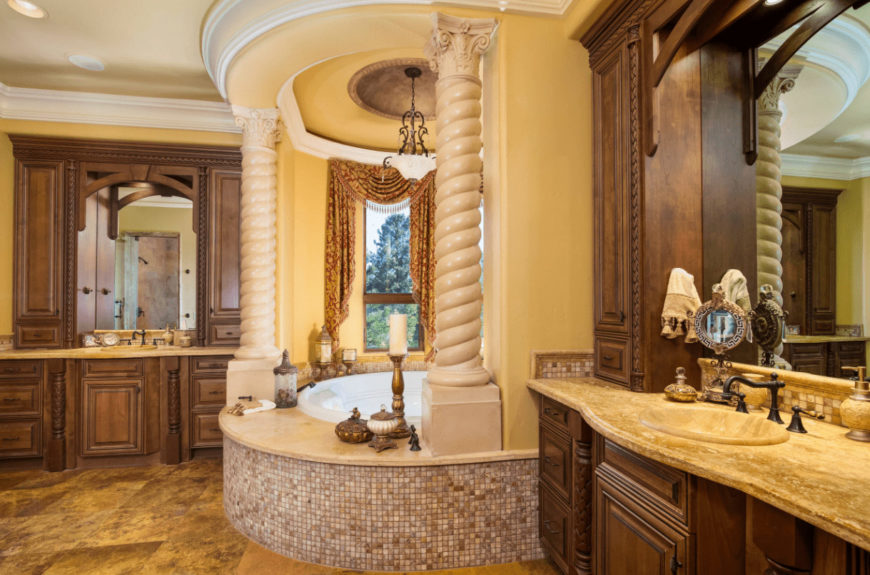 Classy master bathroom with alcove tub and wooden sink vanities topped with limestone counters that complement the tiled flooring.
