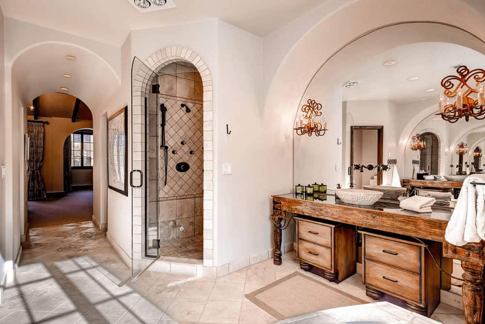 This master bathroom showcases a walk-in shower and natural wood vessel sink vanity with an arched mirror mounted with beautiful candle sconces.