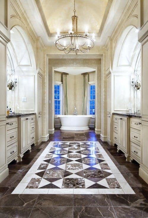 Sophisticated master bathroom illuminated by a candle chandelier that hung from the tray ceiling. It has facing vanities and a freestanding tub at the far end over black marble flooring.