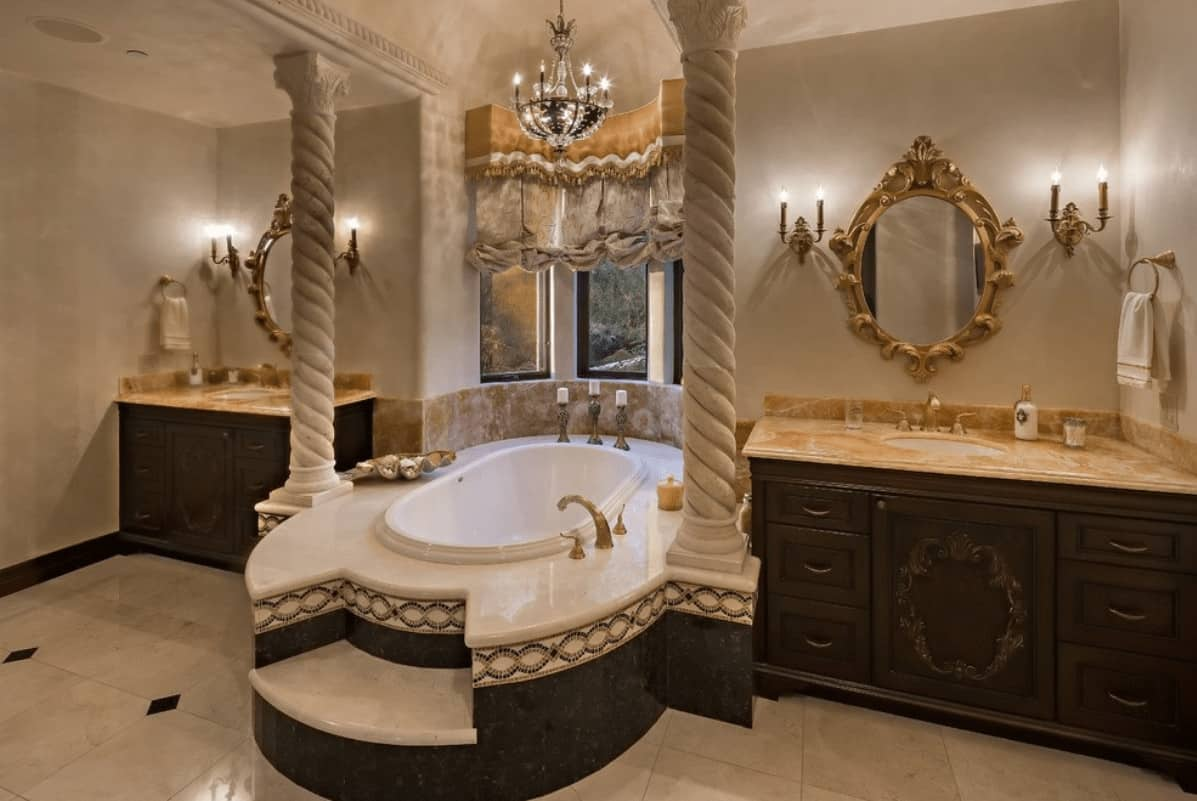 Dark wood vanities paired with gorgeous mirrors flank a drop-in tub lined with spiral columns. It is illuminated by a small fancy chandelier that hung from the beige ceiling.