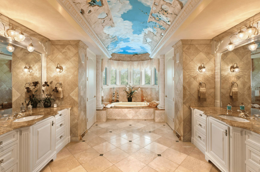 Mediterranean master bathroom with a stunning sky ceiling and marble tiled flooring arranged in a diamond pattern. It includes facing white sink vanities topped with frameless mirrors.