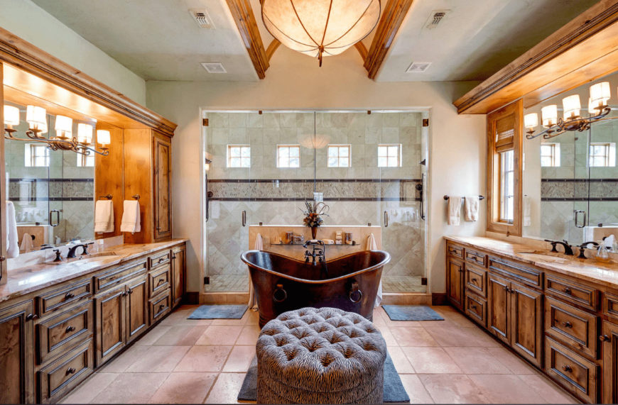 The beige master bathroom features his and her sink vanity along with a walk-in shower and copper freestanding tub accompanied by a round tufted ottoman.