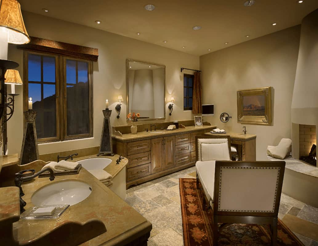 Natural wood vanities, drop-in tub and a kiva fireplace surround a beige cushioned bench that sits on a red bordered rug. This room is illuminated by wall sconces and recessed ceiling lights.