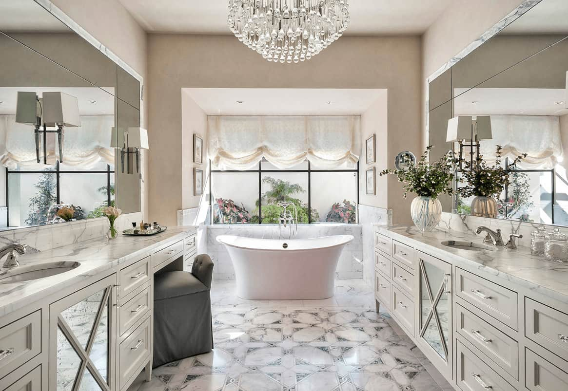 A fancy crystal chandelier adds class in this luxury master bathroom with facing sink vanities and a freestanding tub by the framed window dressed in a charming roman shade.