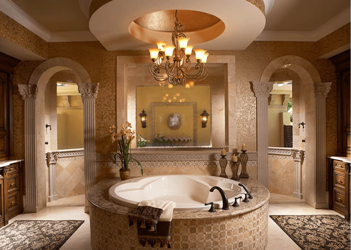 Elegant master bathroom with a round bathtub illuminated by an ornate chandelier that hung from the tray ceiling. It includes classy rugs and arched doors leading to the walk-in shower.