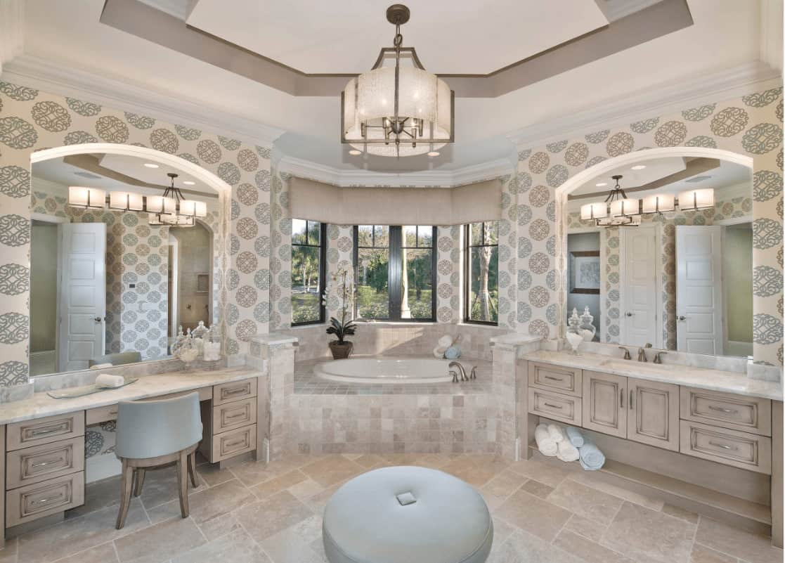 Clad in beige patterned wallpaper, this master bathroom boasts light wood vanities and a deep soaking tub by the bay window overlooking the lush greenery.