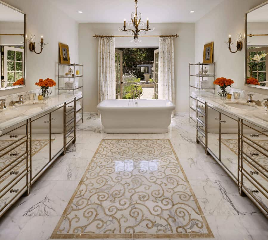 Fabulous master bathroom with mirrored vanities and freestanding tub flanked by shelving units. It has white marble flooring designed with a lovely centerpiece along with a French door that opens to the yard.