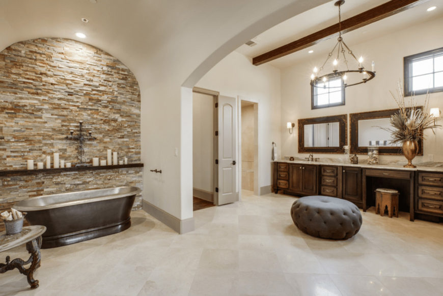 Spacious master bathroom offers a freestanding bathtub and wooden sink vanity accompanied by a gray tufted ottoman that's lighted by a round candle chandelier.